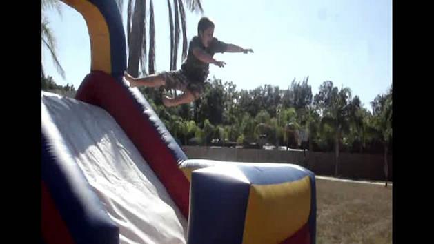 Boy Flips Over Bouncy Slide